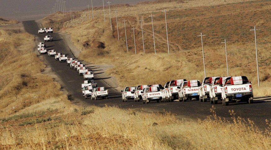 Vehicles of the Kurdish peshmerga forces, carrying coffins containing the remains of Yazidis who were killed by militants of the Islamic State, make their way to Mazar Sharaf al-Din, north of Sinjar Mountain, August 13, 2015. Remains of 68 Yazidis killed by militants of the Islamic State after the fall of their ancient homeland of Sinjar last year were buried in the Shrine of Mazar Sharaf al-Din, north of Sinjar Mountain. REUTERS/Ari Jalal  NO ARCHIVES