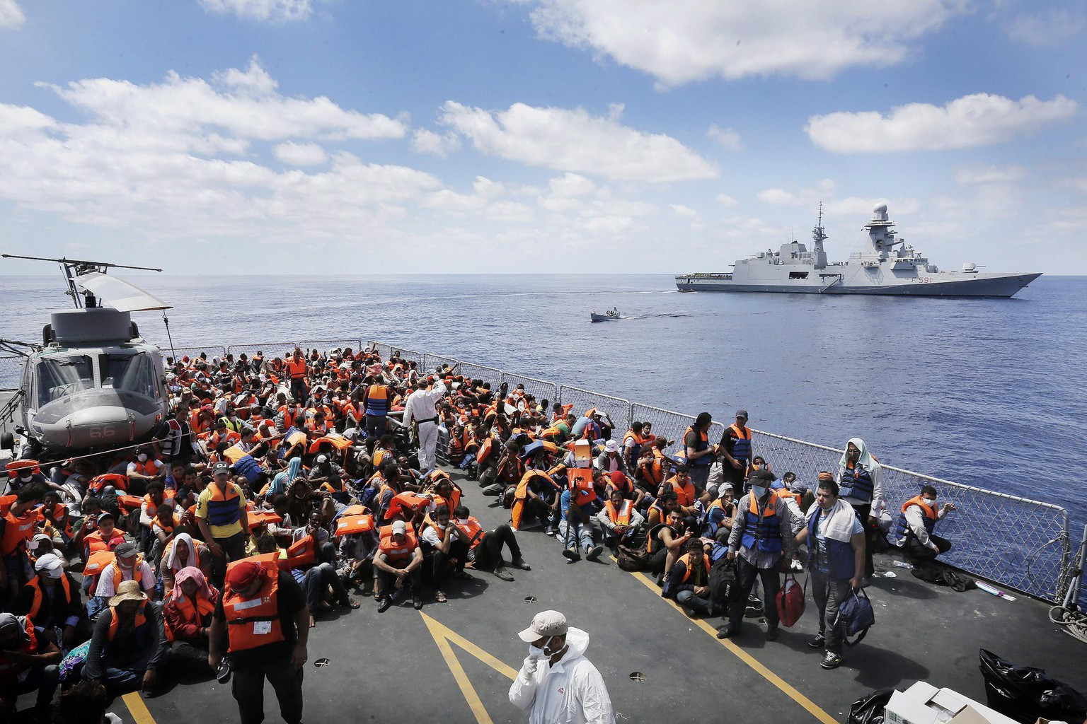 epa04380873 A picture made available on 02 September 2014 shows refugees being transferred from Italian Navy's frigate 'Euro' to 'Virgilio Fasan' (R) within the scope of Mare Nostrum operation in the Southern Mediterranean Sea, 30 August 2014. So far this year, more than 100,000 migrants have landed on Italian shores. Rome authorities have launched a maritime search-and-rescue operation to prevent deaths at sea, but they say they cannot continue funding it on their own.  EPA/GIUSEPPE LAMI