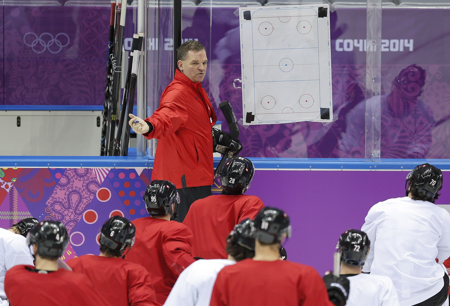 Swiss ice hockey head coach Sean Simpson instructs players during a training session at the Bolshoy Ice Dome at the the 2014 Winter Olympics, Saturday, Feb. 8, 2014, in Sochi, Russia. (AP Photo/Julio Cortez)