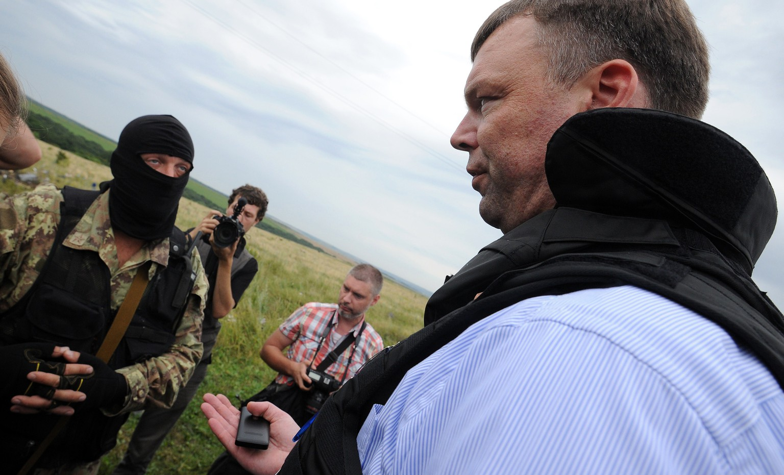 Alexander Hug, (R) Deputy Chief Monitor of the Organization for Cooperation and Security in Europe's (OSCE) Special Monitoring Mission to Ukraine, talks with a Pro-Russian separatist at the site of the crash of a Malaysian airliner carrying 298 people from Amsterdam to Kuala Lumpur in Grabove, in rebel-held east Ukraine, on July 18, 2014. Members of the UN Security Council demanded a full, independent investigation into the apparent shooting down of a Malaysia Airlines jet over Ukraine. AFP PHOTO / DOMINIQUE FAGET