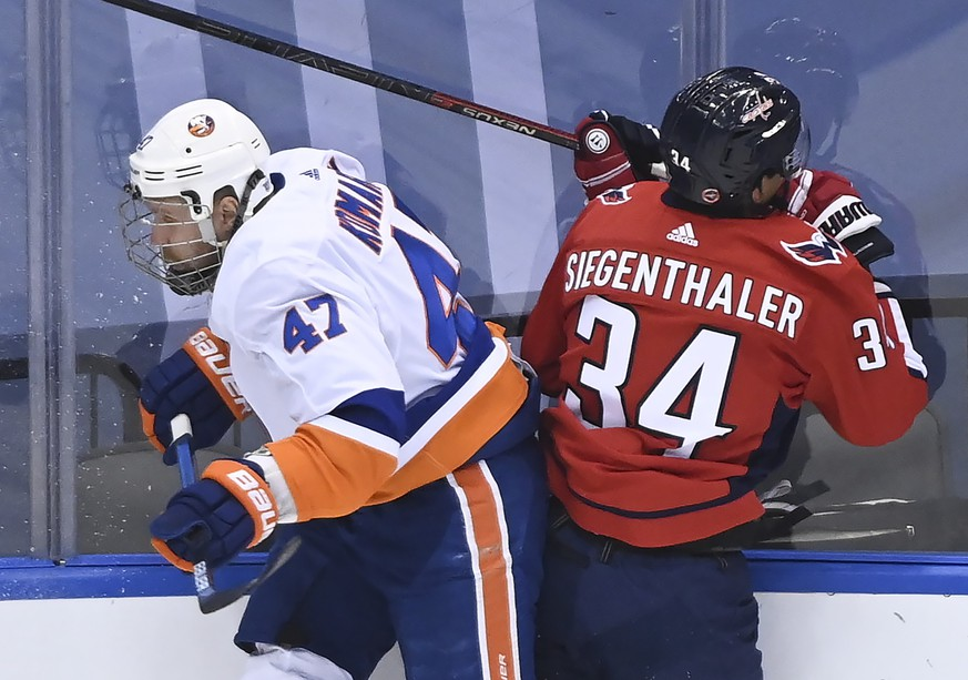 New York Islanders right wing Leo Komarov (47) hits Washington Capitals defenseman Jonas Siegenthaler (34) during the second period of an NHL Eastern Conference Stanley Cup hockey playoff game in Toronto, Wednesday, Aug. 12, 2020. (Nathan Denette/The Canadian Press via AP)