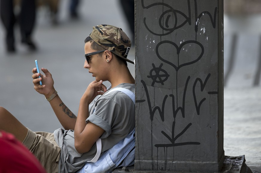 A youth checks his cell phone in Sao Paulo, Brazil, Thursday, Dec. 17, 2015.  Brazilians awoke to a day without WhatApp Thursday after a judge ordered the popular messaging app blocked throughout the country for 48 hours. In a statement, Sao Paulo's criminal court system said only that WhatsApp had been handed two prior judicial orders this year that the California-based company failed to heed. (AP Photo/Andre Penner)
