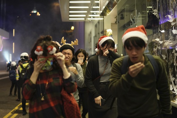 Residents dressed for Christmas festivities react to tear gas as police confront protesters on Christmas Eve in Hong Kong on Tuesday, Dec. 24, 2019. More than six months of protests have beset the city with frequent confrontations between protesters and police. (AP Photo/Kin Cheung)