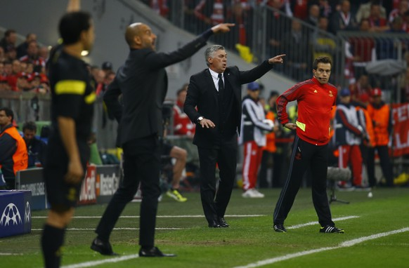 Bayern Munich's coach Josep Guardiola and Real Madrid's coach Carlo Ancelotti  (2nd R) gesture to their players during their Champion's League semi-final second leg soccer match in Munich April 29, 2014.  REUTERS/Kai Pfaffenbach (GERMANY  - Tags: SPORT SOCCER)