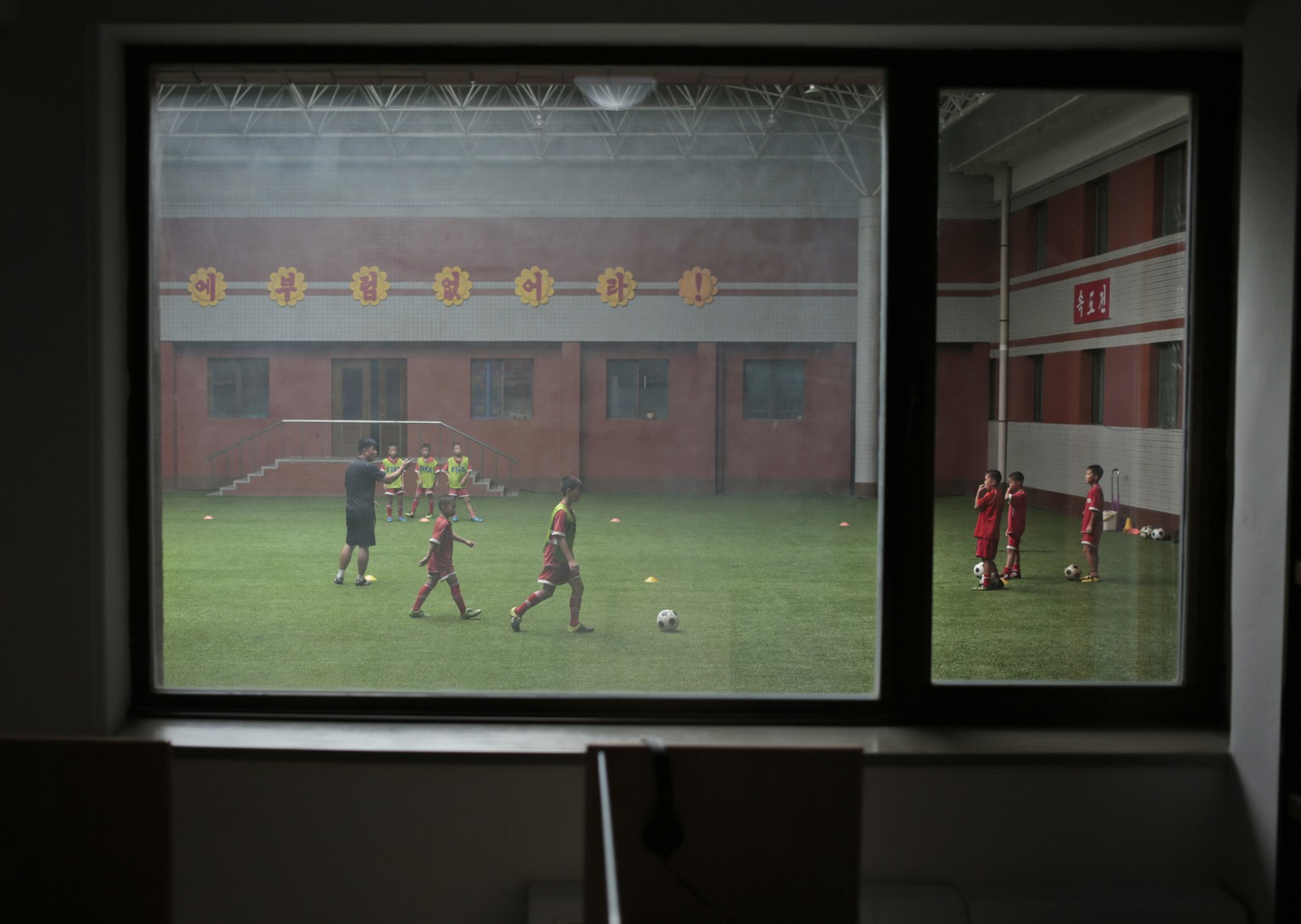 Children practice soccer at Pyongyang International Football School in Pyongyang, North Korea, Wednesday, Aug. 24, 2016. North Korea has poured funds into the development and training of promising athletes over the past several years in an effort to fulfill one of leader Kim Jong Un's primary goals to become a country be reckoned with on the global sports stage. (AP Photo/Dita Alangkara)