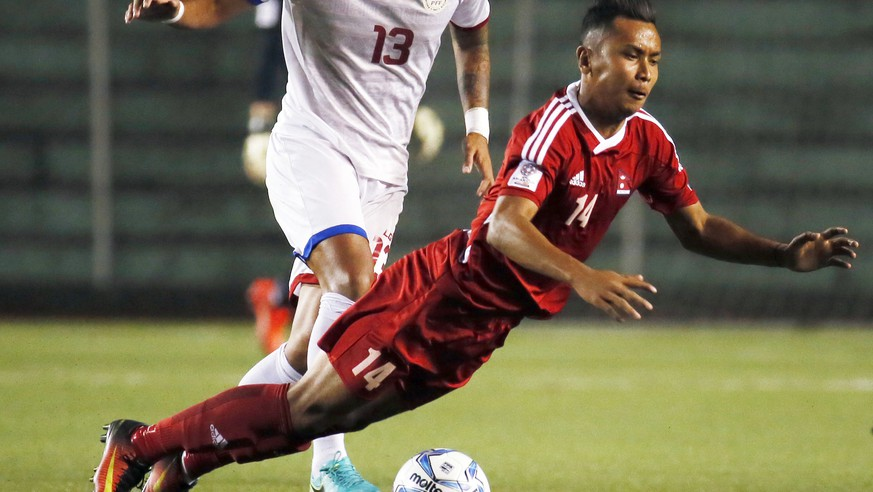 Nepal's Anjan Bista, right, falls after being fouled by Dennis Villanueva of the Philippines during their AFC Asian Cup UAE 2019 Qualifying soccer match Tuesday, March 28, 2017 at the Rizal Memorial Stadium in Manila, Philippines. The Philippines won 4-1. (AP Photo/Bullit Marquez)