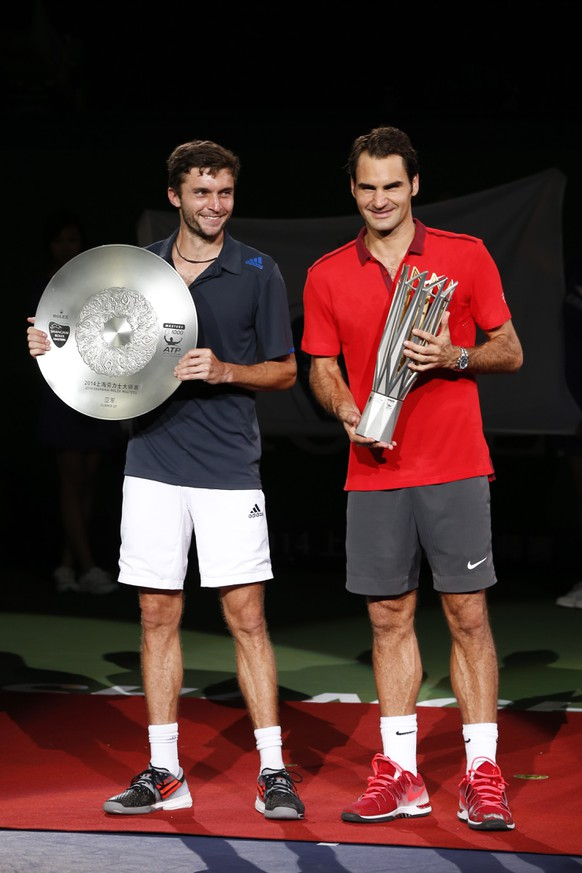 Roger Federer of Switzerland, right, and Gilles Simon of France pose with trophy during the awards ceremony after Federer won the men's singles final at the Shanghai Masters Tennis Tournament in Shanghai, China, Sunday, Oct. 12, 2014.  (AP Photo/Vincent Thian)