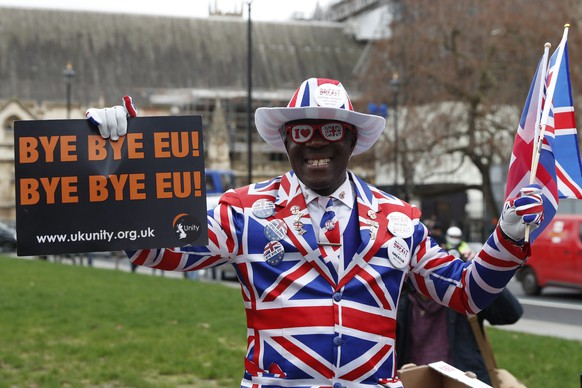A Brexit supports holds a sign in Parliament Square in London, Friday, Jan. 31, 2020. Britain officially leaves the European Union on Friday after a debilitating political period that has bitterly divided the nation since the 2016 Brexit referendum. (AP Photo/Alastair Grant)