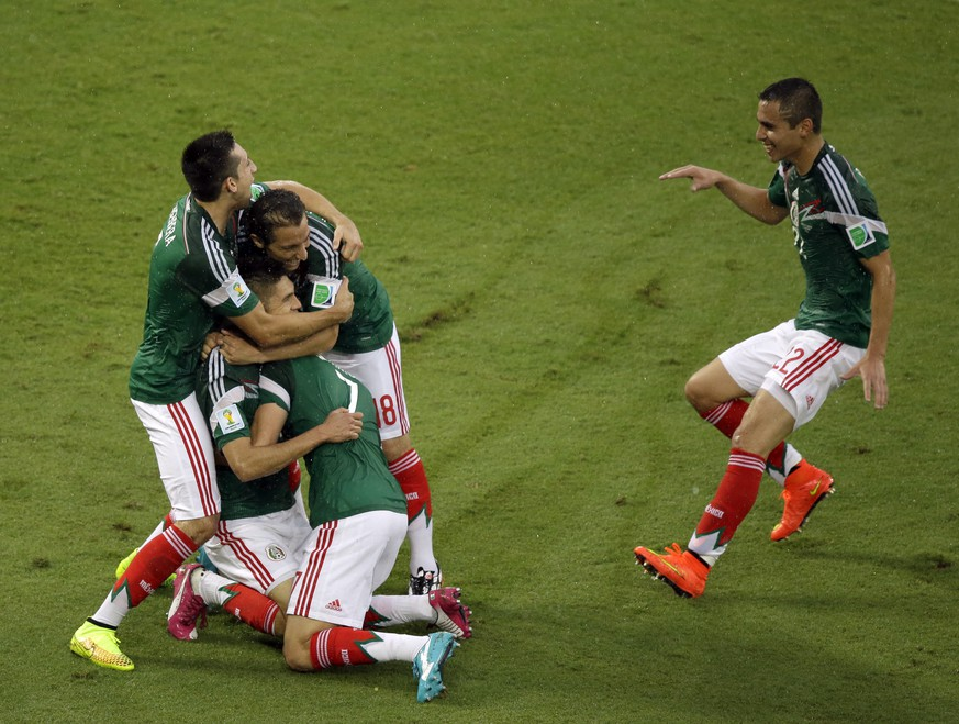 Mexico's players celebrate after Mexico's Oribe Peralta scored during the group A World Cup soccer match between Mexico and Cameroon in the Arena das Dunas in Natal, Brazil, Friday, June 13, 2014.  (AP Photo/Hassan Ammar)