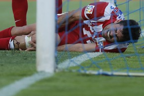 Atletico's Diego Costa, holds his leg as he got injured after scoring during a Spanish La Liga soccer match between Getafe and Atletico Madrid at the Coliseum Alfonso Perez  stadium in Madrid, Spain, Sunday, April 13, 2014. (AP Photo/Andres Kudacki)