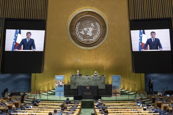 epa08687233 A handout photo made available by UN photo shows Emmanuel Macron (on screens), President of the Republic of France, speaking during the 75th General Assembly of the United Nations, in New York, New York, USA, 21 September 2020. Due to the COVID-19 coronavirus pandemic, the 75th General Assembly of the United Nations meetings are held mostly virutal. Seated at dais are Volkan Bozkir (at left), President of the seventy-fifth session of the United Nations General Assembly, and Secretary-General Antonio Guterres.  EPA/Eskinder Debebe / UN Photo / HANDOUT  HANDOUT EDITORIAL USE ONLY/NO SALES