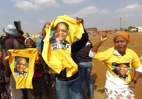 epa04193760 African National Congress (ANC) supporters brandish t-shirts showing South African President Jacob Zuma as they celebrate during a pre-election rally in Bekkersdal near Johannesburg, South Africa, 06 May 2014. The township has been the scene of violent service delivery protests recently. Two decades after South Africa's first democratic elections ended apartheid and swept Nelson Mandela to power, the African National Congress (ANC) that has governed the country since faces its toughest test yet, in the parliamentary poll set for 07 May.  EPA/KIM LUDBROOK