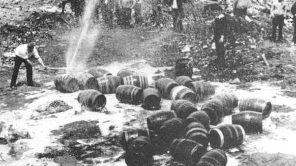FILE - In this June 18, 1931, file photo beer barrels are destroyed by prohibition agents at a dump in New York City. The federal government, as well as state and local authorities, spent huge sums on enforcement yet never allocated sufficient resources to do the job effectively. Bootleggers awash in cash bribed judges, politicians and law enforcement officers to let their operations continue. (AP Photo, File)prohibition