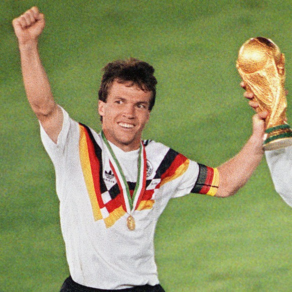 West German midfielder Lothar Matthaeus (L) and forward Pierre Littbarski celebrate with the World Cup trophy after their team beat the defending champions Argentina 1-0 on a penalty kick by defender Andreas Brehme in the World Cup final, 08 July 1990 in Rome. (KEYSTONE/EPA PHOTO/AFP/Str)