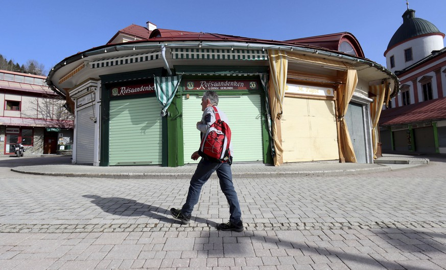 A man walks past a closed shop of a pilgrim market in Mariazell, Austria, Tuesday, Feb. 23, 2021. The Austrian government has moved to restrict freedom of movement for people, in an effort to slow the onset of the COVID-19 coronavirus. (AP Photo/Ronald Zak)