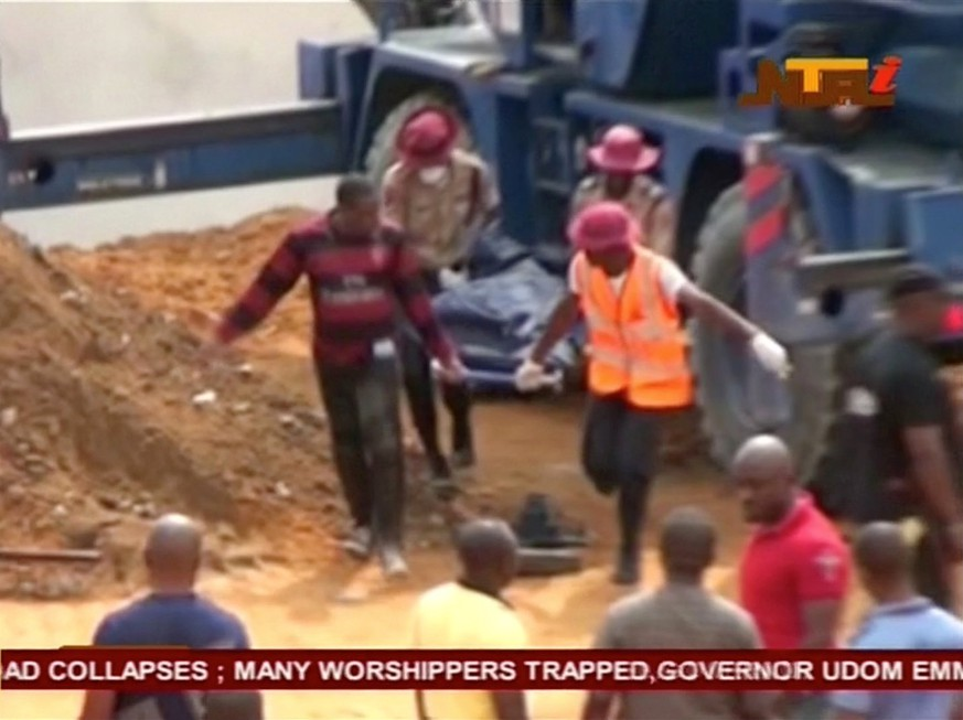 People carry a body on a stretcher after a church collapsed during a service in the southern city of Uyo in Akwa Ibom state, Nigeria in this still image from video December 10, 2016. Video taken December 10, 2016.   NTA via REUTERS TV     ATTENTION EDITORS - THIS IMAGE WAS PROVIDED BY A THIRD PARTY. EDITORIAL USE ONLY. NO RESALES. NO ARCHIVE. NIGERIA OUT. NO COMMERCIAL OR EDITORIAL SALES IN NIGERIA