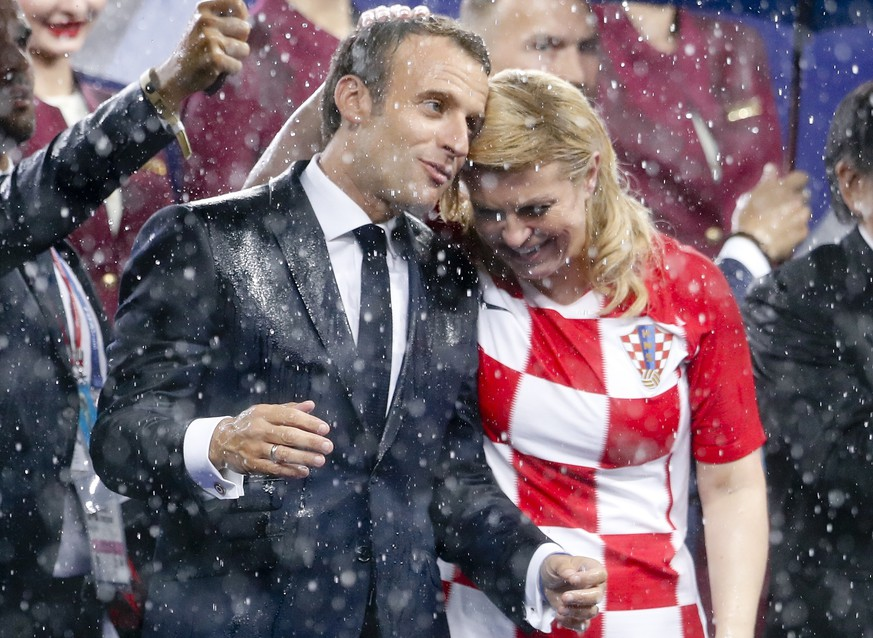 French President Emmanuel Macron and Croatian President Kolinda Grabar-Kitarovic, right, attend the award ceremony at the end of the final match between France and Croatia at the 2018 soccer World Cup in the Luzhniki Stadium in Moscow, Russia, Sunday, July 15, 2018. France won 4-2. (AP Photo/Petr David Josek)