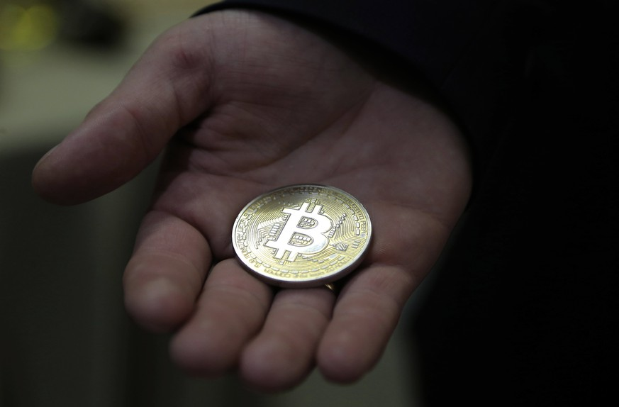 epa06170774 A visitor holds a Bitcoin (virtual currency) souvenir coin, during a webinar by Russian businessman, Orthodox activist and founder the Crypto exchange CryptoSterlingClub Alisa, German Sterligov at the main office of CryptoSterlingClub Alisa in Moscow, Russia, 29 August 2017. According to media reports, Russian Finance Ministry stated that cryptocurrencies like bitcoin are a high risky 'financial pyramid' and trading should be limited to only 'qualified investors'. The CryptoSterlingClub Alisa was opened on 24 August 2017.  EPA/MAXIM SHIPENKOV