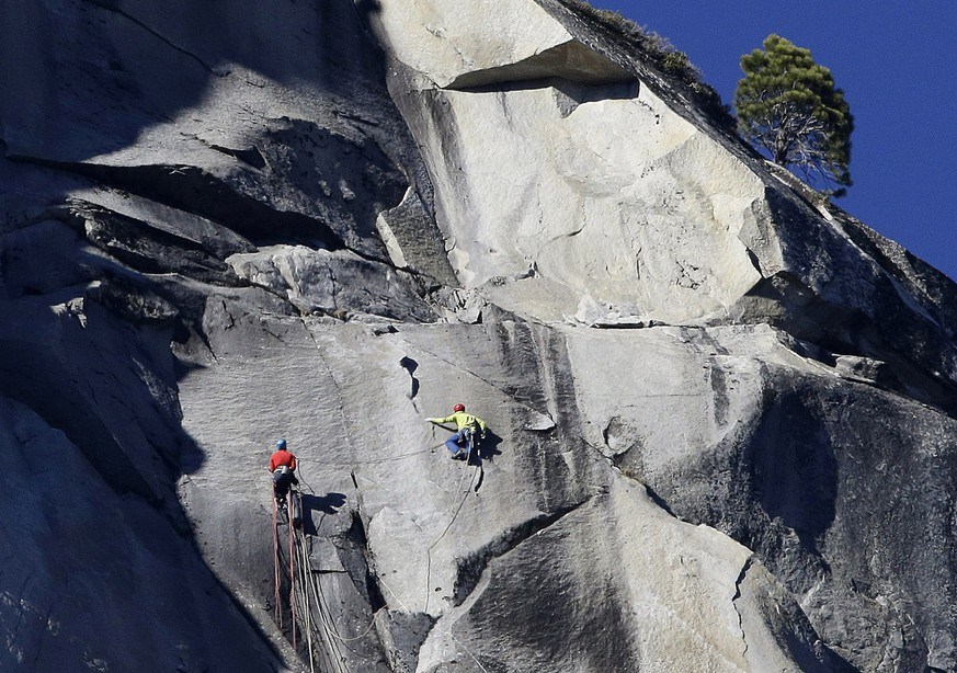 Kevin Jorgeson, left, and Tommy Caldwell climb El Capitan, Wednesday, Jan. 14, 2015, as seen from the valley floor in Yosemite National Park, Calif. Caldwell and Jorgeson became the first to free-climb the rock formation's Dawn Wall. They used ropes and safety harnesses to catch them in case of a fall, but relied entirely on their own strength and dexterity to ascend by grasping cracks as thin as razor blades and as small as dimes. (AP Photo/Ben Margot)