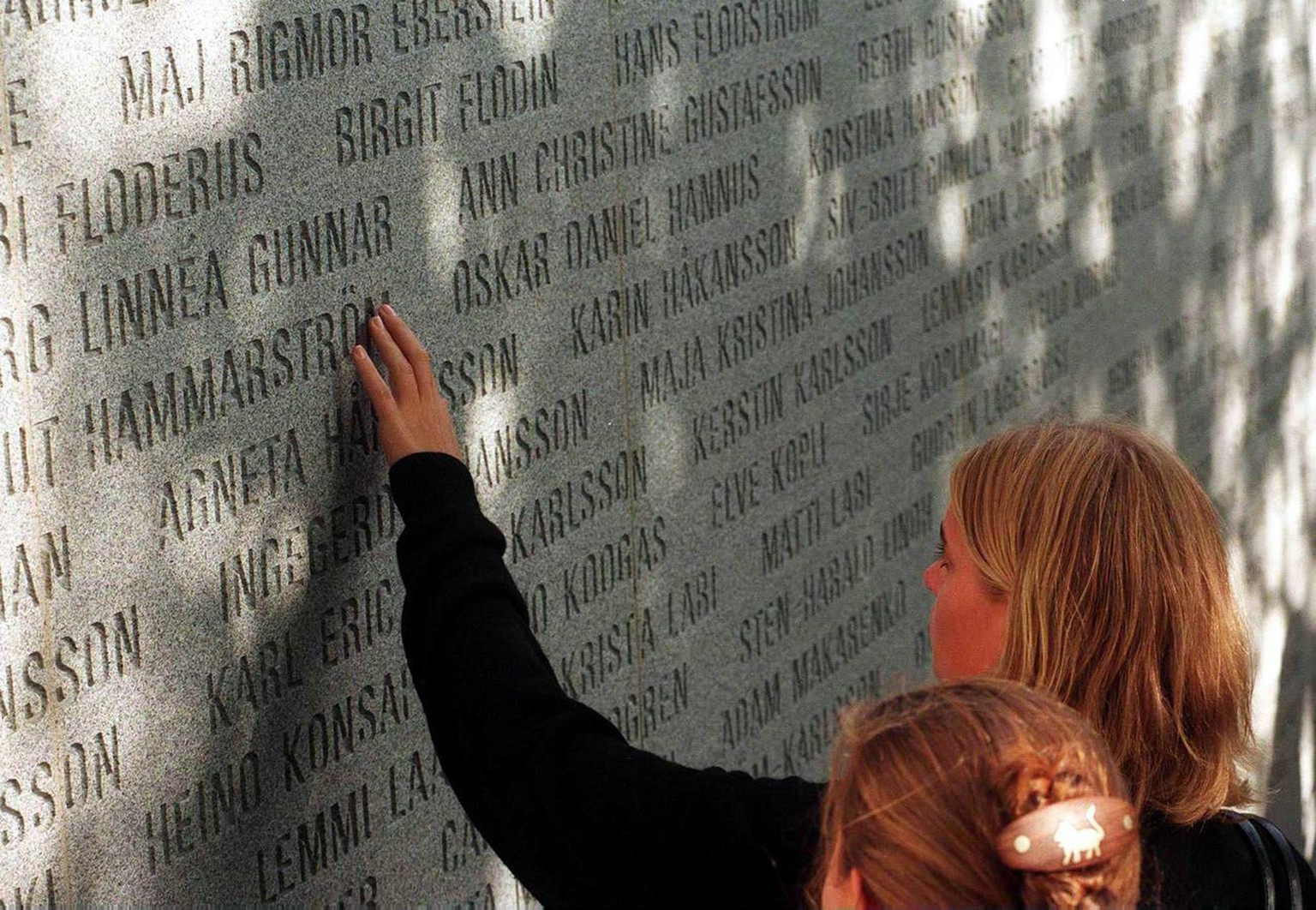 A unidentified relative of the 1994 Estonia ferry disaster victim reads a name on the monument wall downtown Stockholm 28 September 1997. A monument commemorating the 852 victims of the Estonia ferry disaster off Finish coast was today unveiled here, on the third anniversary of the accident. (KEYSTONE/EPA/PRESSENS/HENRIK MONTGOMERY)