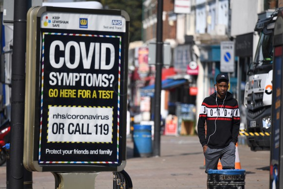 epa08670849 Pedestrians walk past a sign displaying a Covid helpline in London, Britain, 15 September 2020. In order to curb the rise in coronavirus cases in the UK, it is now illegal for groups of more than six to meet up. The 'rule of six' have been implemented in the latest push to curb the recent surge in coronavirus infections in the United Kingdom.  EPA/FACUNDO ARRIZABALAGA