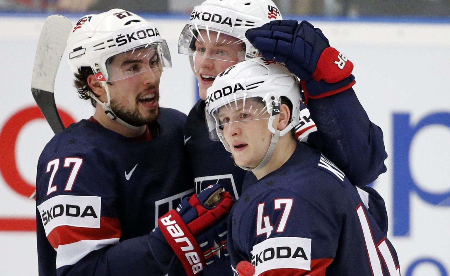 epa04744988 Justin Faulk (L), Jack Eichel (C) and Torey Krug (R) of the USA celebrate their victory after scoring a golden goal at the Ice Hockey World Championship 2015 group B match between the USA and Slovakia at CEZ Arena in Ostrava, Czech Republic, 12 May 2015.  EPA/ARMANDO BABANI