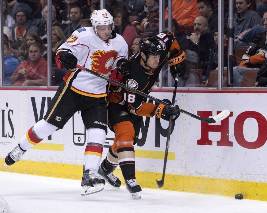 Anaheim Ducks' Tim Jackman, right, controls the puck as the Calgary Flames' Sven Baertschi defends during an NHL hockey game Tuesday, Nov. 25, 2014, in Anaheim, Calif. (AP Photo/The Orange County Register, Kyusung Gong)   MAGS OUT; LOS ANGELES TIMES OUT