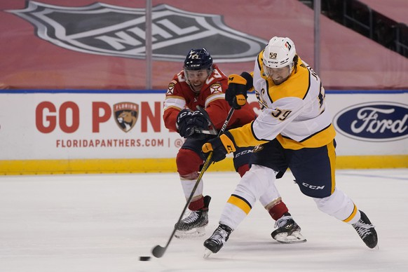 Nashville Predators defenseman Roman Josi (59) shoots as Florida Panthers center Carter Verhaeghe (23) defends during the third period of an NHL hockey game, Friday, Feb. 5, 2021, in Sunrise, Fla. (AP Photo/Wilfredo Lee) Carter Verhaeghe,Roman Josi