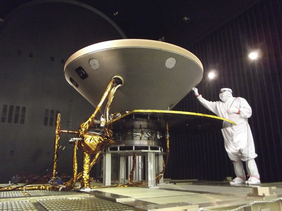 """In this 2015 photo made available by NASA, a technician prepares the InSight spacecraft for thermal vacuum testing in its """"cruise"""" configuration for its flight to Mars, simulating the conditions of outer space at Lockheed Martin Space Systems in Denver. NASA's three-legged, one-armed geologist known as InSight makes its grand entrance through the rose-tinted Martian skies on Monday, Nov. 26, 2018.  (NASA/JPL-Caltech/Lockheed Martin via AP)"""