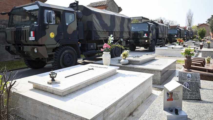 A convoy of Italian Army trucks arrives from Bergamo carrying bodies of coronavirus victims to the cemetery of Ferrara, Italy, where they will be cremated, Saturday, March 21, 2020. The transfer was made necessary since Bergamo mortuary reached maximum capacity. For most people, the new coronavirus causes only mild or moderate symptoms. For some it can cause more severe illness, especially in older adults and people with existing health problems. (Massimo Paolone/LaPresse via AP)