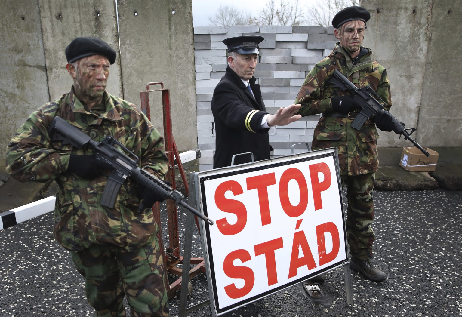Demonstrators hold banners on the Northern Ireland/Republic of Ireland border, near Newry in Northern Ireland, Saturday, Jan. 26, 2019. Protesters angered at the prospect of a hard Brexit built a mock wall across part of the Irish border, the theatrical gesture on Saturday was the centrepiece of a County Down demonstration against future border checks. (AP Photo/Peter Morrison)