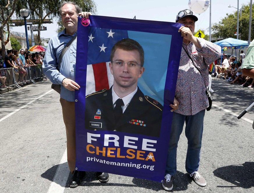 Men carry a sign urging freedom for convicted national security leaker Pvt. Chelsea Manning during the 44th annual Los Angeles Pride parade in West Hollywood, California June 8, 2014. Manning, formerly named Bradley, was convicted of sending classified documents to anti-secrecy website WikiLeaks.  REUTERS/Jonathan Alcorn   (UNITED STATES - Tags: SOCIETY POLITICS)