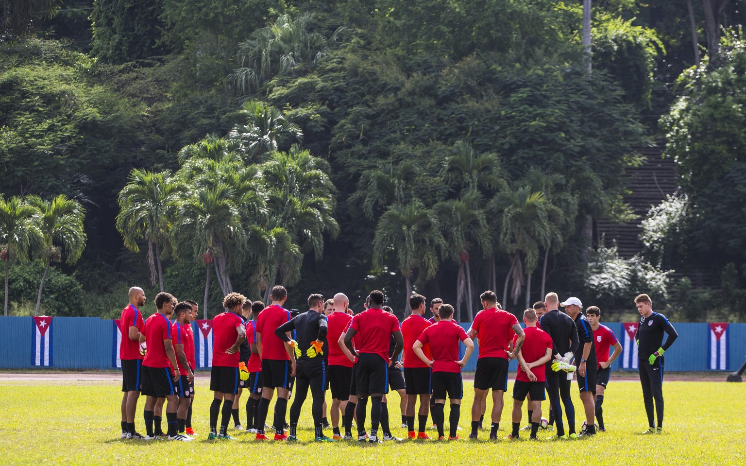 The United States national soccer team coach Jurgen Klinsmann, at right with white cap, gives instructions to his players during a training session at Pedro Marrero Stadium in Havana, Cuba, Thursday, Oct. 6, 2016. Cuba will play a friendly soccer match with the U.S. on Friday Oct. 7. (AP Photo/Desmond Boylan)