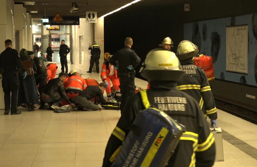 Firefighters treat an injured person at a subway station in Hamburg, Germany, Thursday, April 12, 2018. Police say a woman and her child have died after being stabbed by her ex-husband at a subway station in central Hamburg. The knife attack happened Thursday morning at the Jungfernstieg station in Germany's second-biggest city.  (Tnn/dpa via AP)