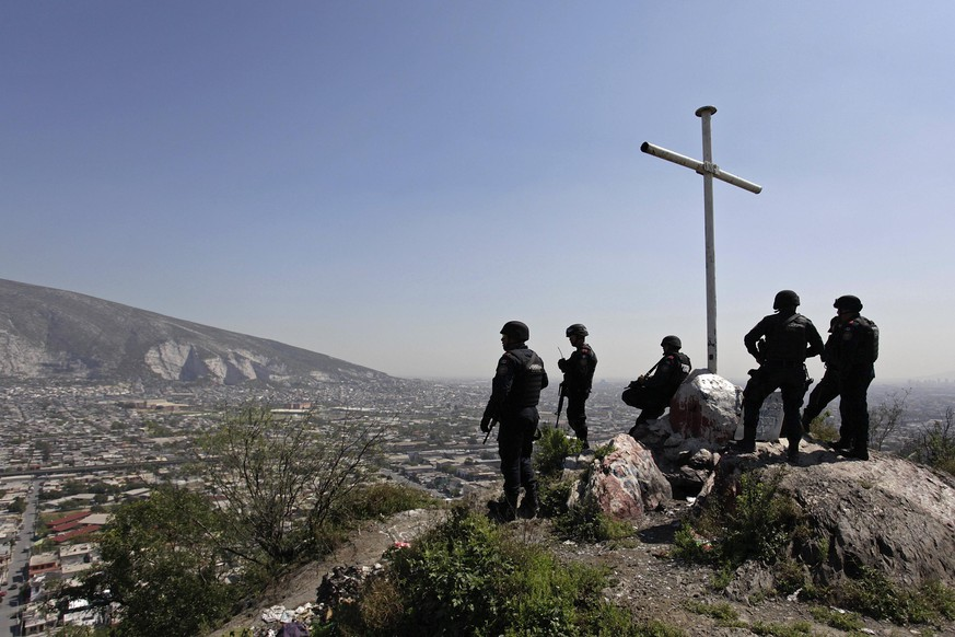 Members of the Fuerza Civil (Civil Force) police unit gather at a cross during a patrol at an impoverished neighbourhood in Monterrey February 26, 2015. Fuerza Civil, a tactical team of the police unit trained by the army, was created by the Nuevo Leon government in 2011 to curb down corruption and infiltration by drug gangs in the police corps, local media reported. Promising a new law to stop the infiltration of local governments by organized crime, President Enrique Pena Nieto pledged to reform the penal system and send a proposal to Congress to unify multi-layered police forces in Mexico's 31 states, taking Fuerza Civil as the police model that the federal government wants for the rest of the country. REUTERS/Daniel Becerril (MEXICO - Tags: CIVIL UNREST POLITICS CRIME LAW)