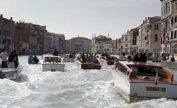 The water-taxi carrying George Clooney and his fiancee Amal Alamuddin, center, cruise along the Grand Canal in Venice, Italy, Friday, Sept. 26, 2014. George Clooney and his fiancee Amal Alamuddin arrived in Venice on Friday for their weekend wedding extravaganza, accompanied by loved ones and trailed by a clutch of photographers who recorded their passage along the picturesque Grand Canal. (AP Photo/Luca Bruno)