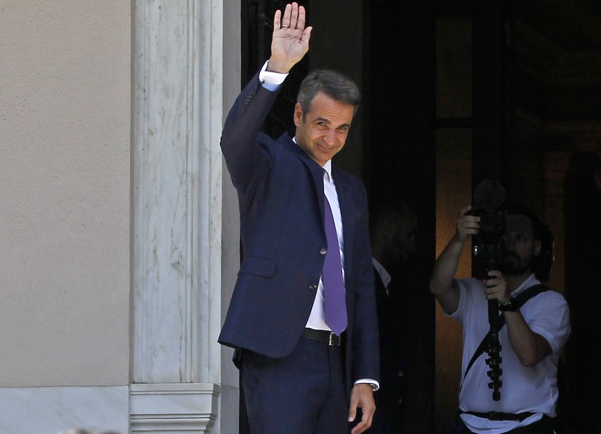 epa07703263 Newly appointed Prime Minister Kyriakos Mitsotakis waves to the outgoing Prime Minister Alexis Tsipras (not pictured) outside Maximos Mansion in Athens, Greece, 08 July 2019. New Democracy won general elections in Greece on 07 July and will form a majority government. A total of six parties will enter parliament based on the results. Voter participation reached 57.92 percent.  EPA/ALEXANDROS VLACHOS