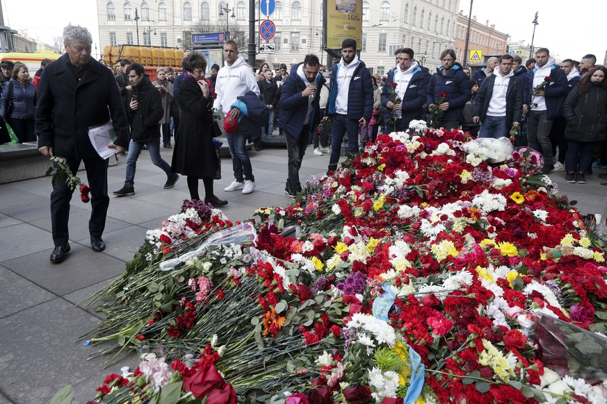 Zenit's St.Petersburg soccer club head coach Mircea Lucescu, left, and club players lay flowers at a symbolic memorial at Technologicheskiy Institute subway station in St. Petersburg, Russia, April 5, 2017. A bomb blast tore through a subway train deep under Russia's second-largest city St. Petersburg Monday, killing several people and wounding many more in a chaotic scene that left victims sprawled on a smoky platform. (AP Photo/Dmitri Lovetsky)
