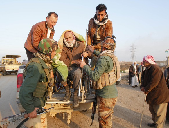 Kurdish security forces help an elderly man from the minority Yazidi sect, seated in a truck, on the outskirts of Kirkuk January 17, 2015. Islamic State freed around 350 members of Iraq's Yazidi minority on Saturday, delivering them to safety in the country's Kurdish north. REUTERS/Ako Rasheed (IRAQ - Tags: POLITICS MILITARY CIVIL UNREST CONFLICT SOCIETY) - RTR4LTPR