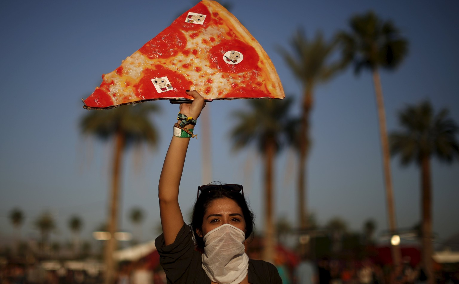 A woman carries a replica slice of pizza, in order to find separated friends in the crowd, at the Coachella Valley Music and Arts Festival in Indio, California April 12, 2015. REUTERS/Lucy Nicholson