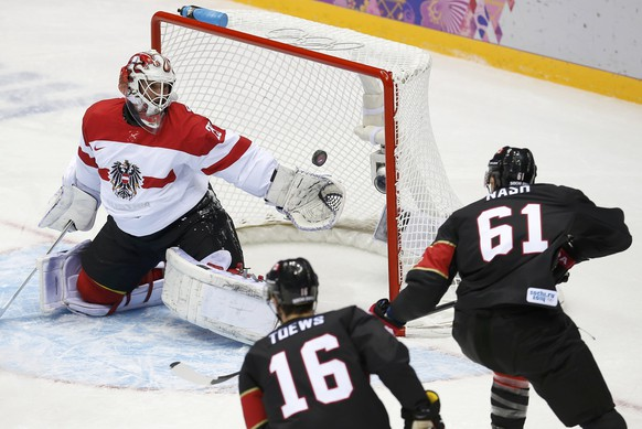 Austria's goalie Bernhard Starkbaum makes a save while Canada's Jonathan Toews and Rick Nash wait for the rebound during the first period of their men's preliminary round ice hockey game at the 2014 Sochi Winter Olympics, February 14, 2014. REUTERS/Jim Young (RUSSIA  - Tags: OLYMPICS SPORT ICE HOCKEY)