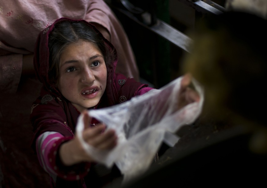A Pakistani poor girl extends her plastic bag to receive free food for her family, distributed at local shrine in suburbs of Islamabad, Pakistan, Friday, Nov. 20, 2015. Pakistan also observed Universal Children's Day, which is marked annually by the United Nations with other nations. (AP Photo/B.K. Bangash)