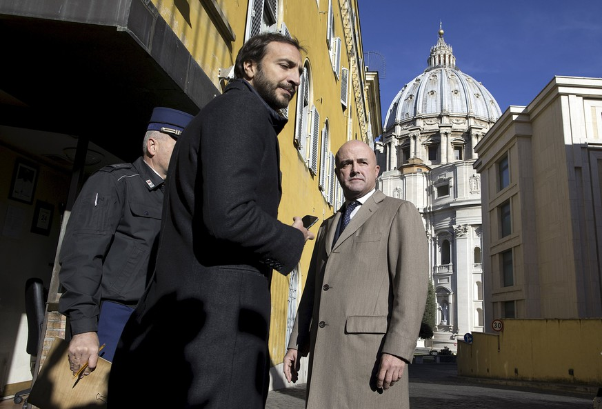 Journalists Gianluigi Nuzzi (R) and Emiliano Fittipaldi (C) arrive at the Vatican November 24, 2015. The Vatican on Saturday ordered five people, including two Italian journalists, to stand trial for leaking and publishing secret documents, in the latest development in a scandal which is rocking the papacy. Causing embarrassment and anger in the Vatican, the two journalists used the leaks by Vatican officials in their books, which the Holy See described as giving a