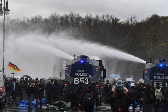 epa08827234 Riot police use water cannons to break up a demonstration against German coronavirus restrictions, near the Brandenburg Gate in Berlin, Germany, 18 November 2020. While German interior minister prohibited demonstrations around the Reichstag building during the parliamentary Bundestag session people gathered to protest against government-imposed semi-lockdown measures aimed at curbing the spread of the coronavirus pandemic. Since 02 November, all restaurants, bars, cultural venues, fitness studious, cinemas and sports halls are forced to close for four weeks as a lockdown measure to rein in skyrocketing coronavirus infection rates.  EPA/FILIP SINGER