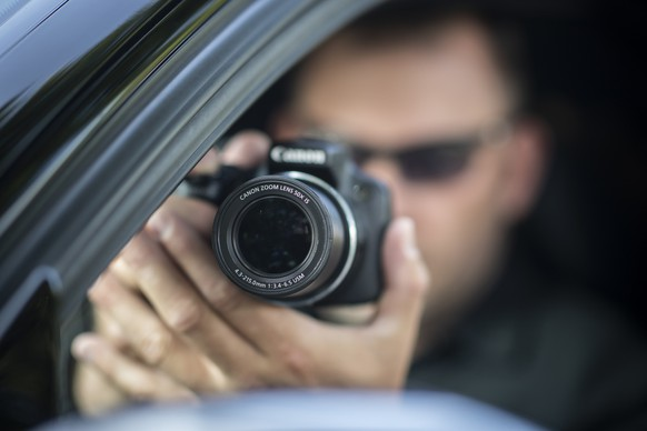 ARCHIV – ZUM 1. PAROLENSPIEGEL ZU DEN EIDGENOESSISCHEN ABSTIMMUNGEN VOM 25. NOVEMBER 2018 STELLEN WIR IHNEN FOLGENDES BILDMATERIAL ZUR VERFUEGUNG - [Symbolic Image, Staged Picture] A professional private detective of the detective agency investigo takes pictures from inside his car, pictured in Otelfingen, Canton of Zurich, Switzerland, on June 8, 2018. (KEYSTONE/Ennio Leanza)