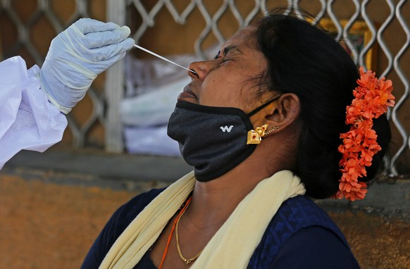 epa09161638 A health worker takes a nasal swab sample of a woman for COVID-19 test in Bangalore, India, 26 April 2021. The Karnataka government is contemplating a partial lockdown of the city in the wake of rising Covid-19 cases, extending the night curfew and imposed a weekend curfew which includes closure of cinema halls, bars and pubs, gyms and colleges. India recorded a massive surge of 352,991 fresh Covid-19 cases and 2,812 deaths, the highest single-day spike in COVID-19 infections.  EPA/JAGADEESH NV