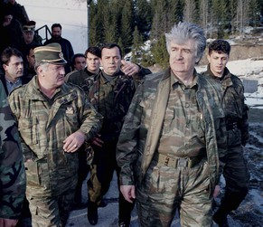 "FILE - In this April 15, 1995 file photo, Bosnian Serb wartime leader, Radovan Karadzic, second right, and his general Ratko Mladic, first left, walk accompanied by bodyguards on Mount Vlasic frontline in Serbia. Mladic has slammed the United Nations' Yugoslav war crimes tribunal as a ""satanic court"" and refused to testify as a defense witness for his former political master Karadzic in the Hague, Netherlands, Tuesday, Jan. 28, 2014. A courtroom reunion of the two alleged chief architects of Serb atrocities during Bosnia's 1992-95 war, lasted only about an hour as Mladic told judges repeatedly he would not answer former Bosnian Serb President Karadzic's questions. (AP Photo/Sava Radovanovic, File)"