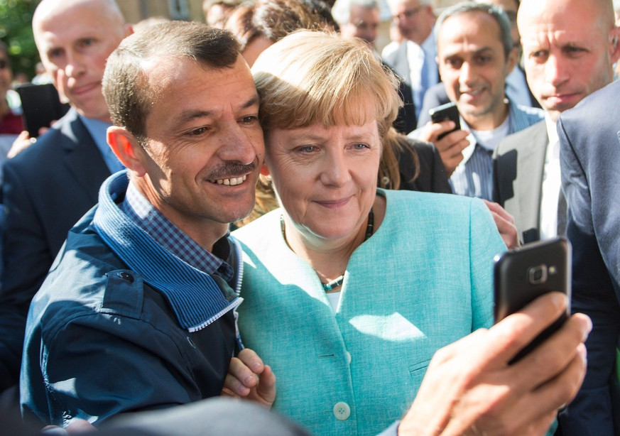 epa04923489 German Chancellor Angela Merkel (R) has a selfie taken with a refugee during a visit to a refugee reception centre in Berlin, Germany, 10 September 2015. Germany can deal with the arrival of hundreds of thousands of refugees without cutting social welfare benefits or raise taxes, Vice Chancellor Sigmar Gabriel said on 10 September, during a debate in parliament on next year's budget. Germany expects 800,000 asylum seekers this year, four times more than last year and more than any other country in the European Union, which is split on how to deal with the biggest refugee crisis since World War II.  EPA/BERND VON JUTRCZENKA