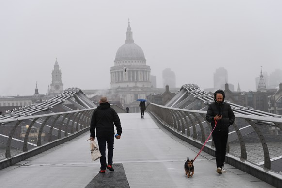epa08935158 Pedestrians walk in the Millennium bridge during third national lockdown in London, Britain, 13 January 2021. A national lockdown across England began on midnight on 05 January 2021. 2020 saw the largest increase in UK deaths in a single year since 1940, according to provisional ONS figures. In 2020, nearly 697,000 deaths were registered, compared with an average of nearly 606,000 each year between 2015 and 2019.  EPA/FACUNDO ARRIZABALAGA
