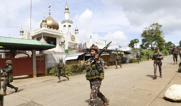 epa05988208 Filipino soldiers conduct a patrol following reports of fresh clashes between government troops and rebels in Marawi City, Mindanao Island, southern Philippines, 25 May 2017. According to media reports, President Rodrigo Duterte declared martial law on the southern island of Mindanao in response to a new armed offensive by the Maute group, one of the jihadist bands operating in the region. On May 23, militants from the Maute group - an organization linked to the so-called Islamic State (or IS or ISIS) - had captured Marawi, a city with a population of 200,000 people, and laid siege on a hospital for hours, and set a church, a college and the city's prison to fire, while holding over 10 people hostage. The Maute group is an Islamic armed organization based in Lanao del Sur that first emerged in 2012 under the name of Khilafah Islamiyah Movement (KIM), but adopted the name EI-Ranao two years later to indicate its affiliation with the so-called Islamic State.  EPA/JEOFFREY MAITEM